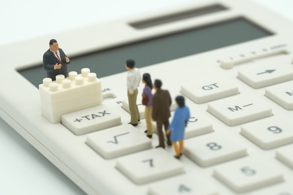 miniature people lined up facing man in suit standing on a calculator