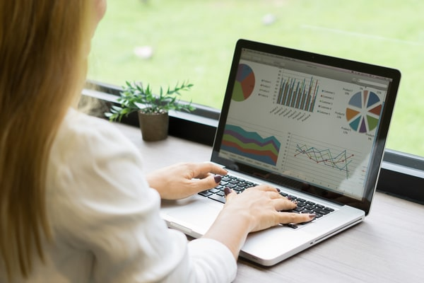 woman on laptop looking at data charts