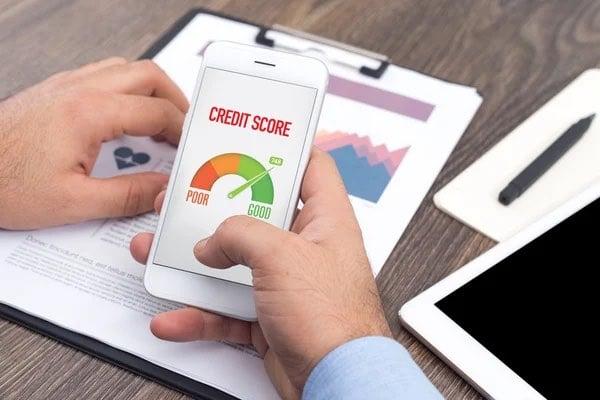 man checks his credit score on his phone
