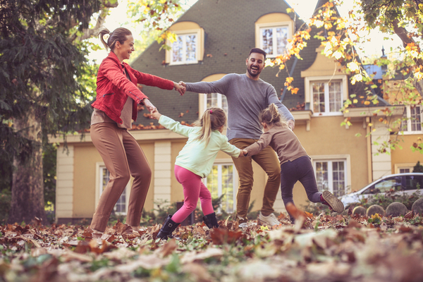 family of 4 holding hands playing in leaves in front of a house