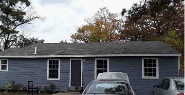 single-story gray house with 2 cars in front