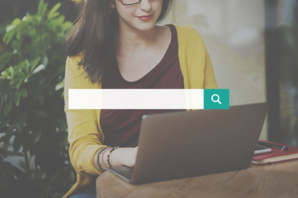 search box over woman using laptop on a table