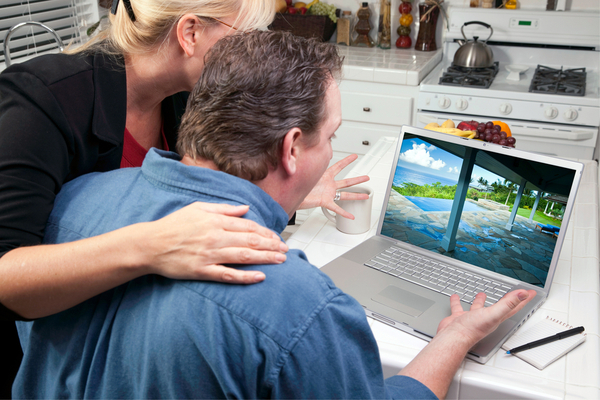 couple look at house picture on their laptop in the kitchen and exclaim