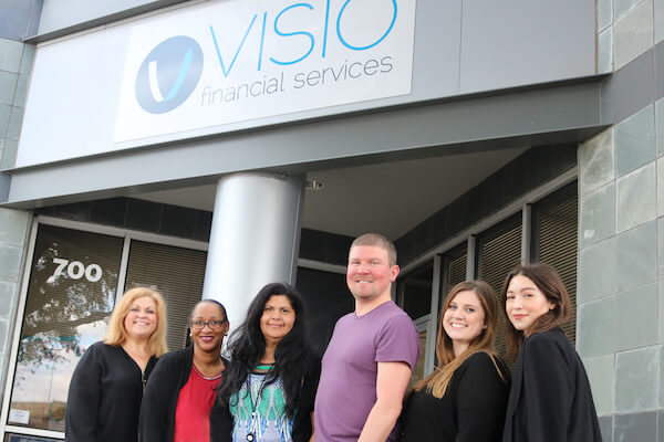 6 people stand under a Visio sign