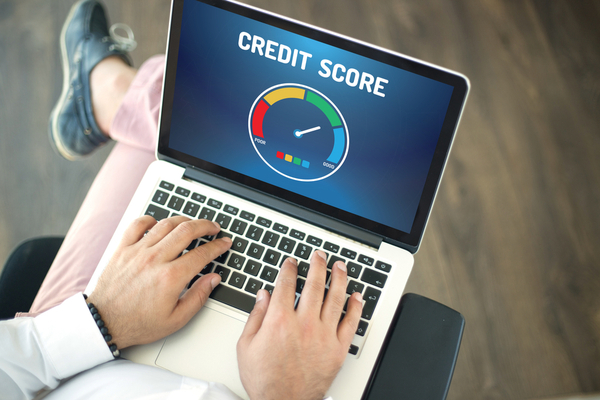 person with laptop on their lap looking at a credit score meter