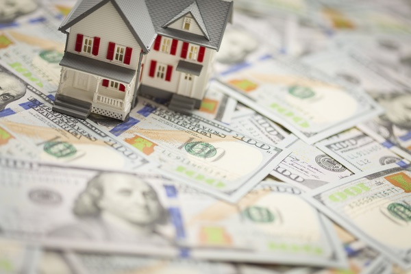 miniature house sitting on dollar bills