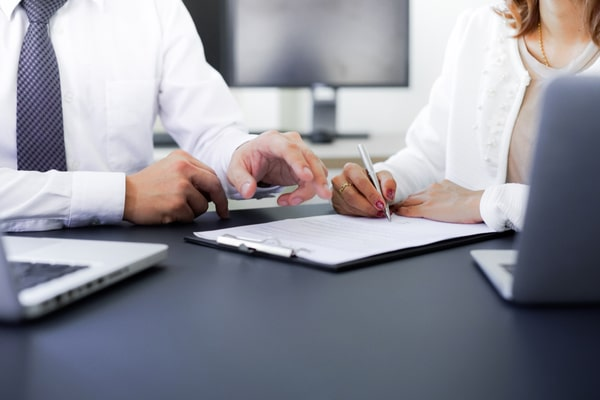man and woman at table gesture at and write on clipboard