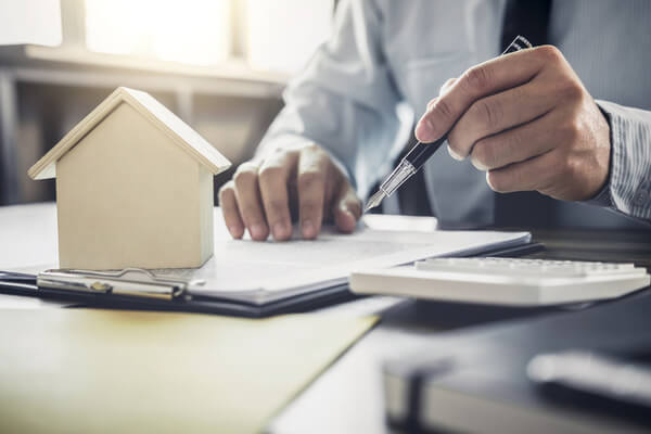 person with pen points to clipboard with model house on it
