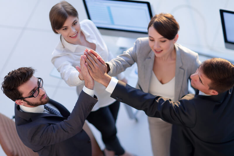 4 people in suits high five