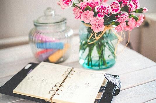 calendar notebook on a table with flowers in a vase
