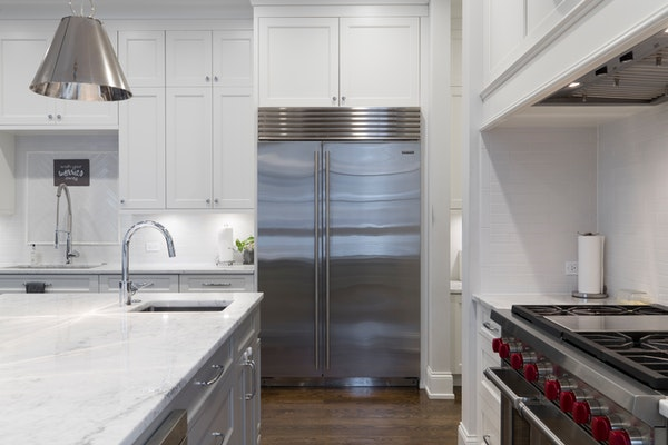 silver refrigerator in a white kitchen with stove and sink