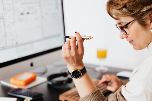 woman looking at computer with watch on