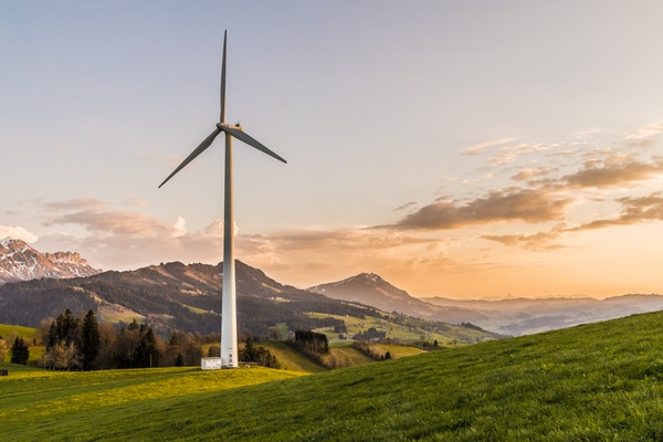 a windmill standing on a green hill with mountains in the background