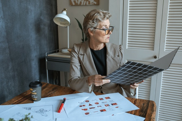 woman with designs on her desk looking through folder