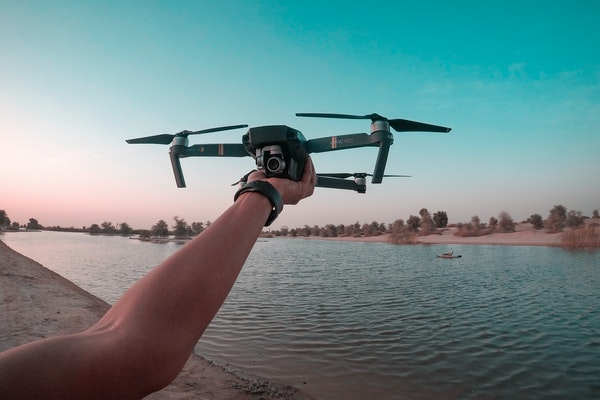 hand holds a drone above a pond
