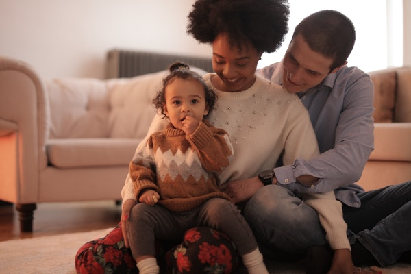 parents and a child sitting on the floor smiling