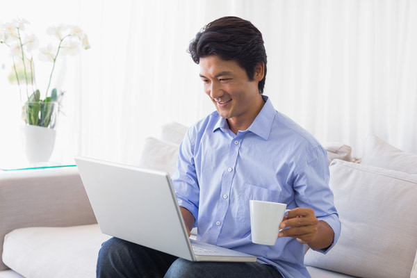 man sits at laptop with drink