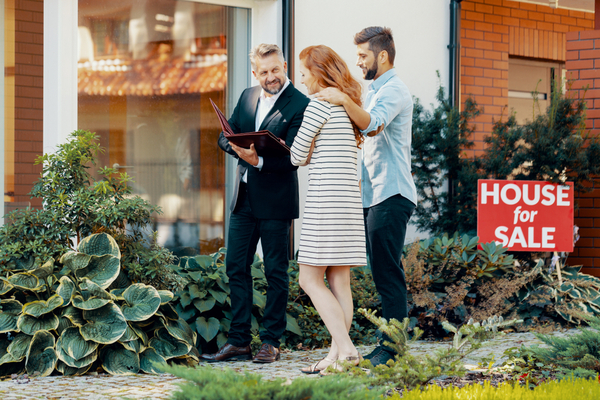 man in suit talks to couple in front of building with