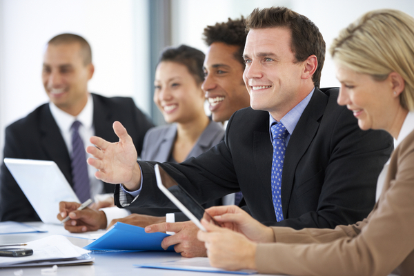 5 people in suits smiling at a meeting