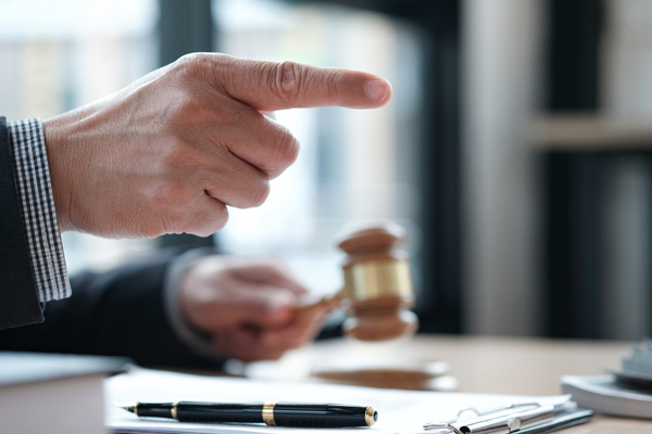 finger points and other hand holds gavel