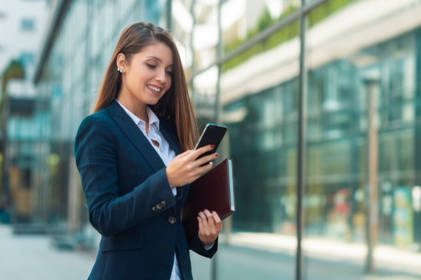 woman in suit looking at phone and smiling outside