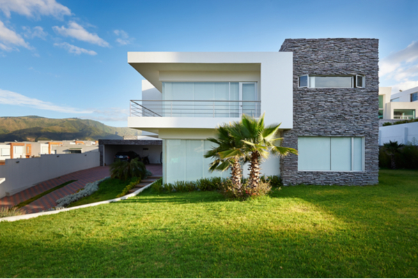stone and white modern house with lawn and red driveway