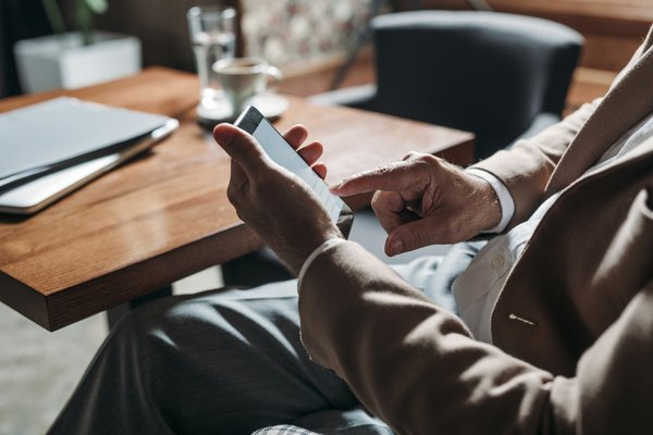 man in suit sitting at table looking at phone screen
