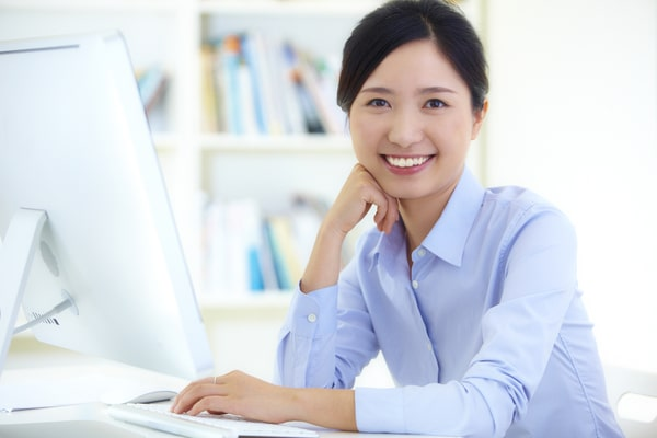 woman in blue shirt smiling at computer