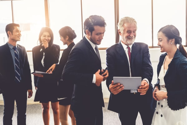 6 people in suits talking and showing each other tablet screens