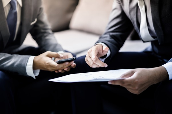 2 people in suits look at information on a paper