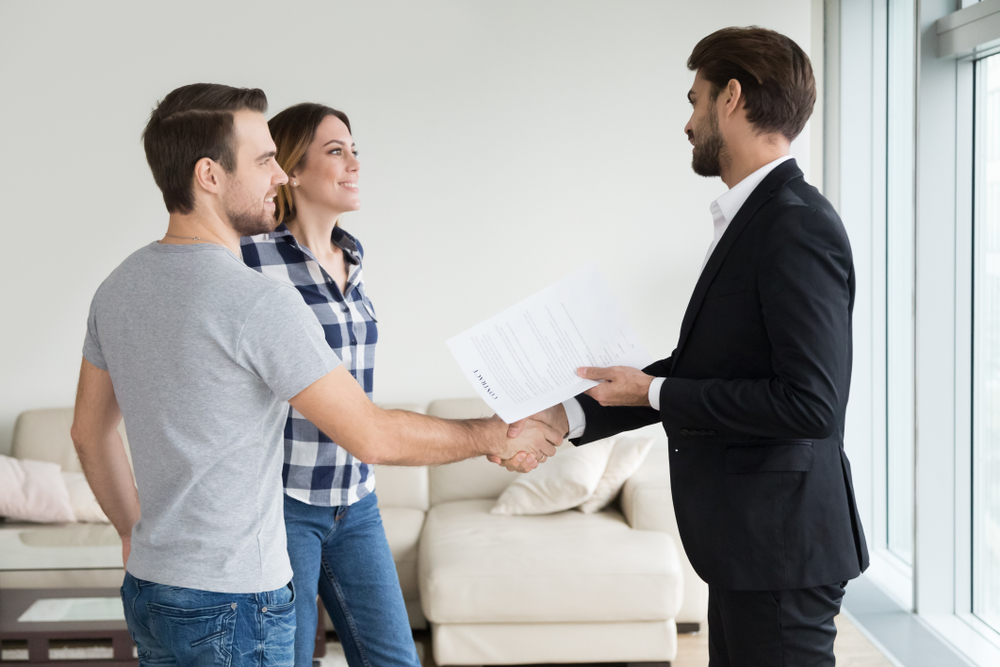 man in a suit shakes hands with a couple in an apartment